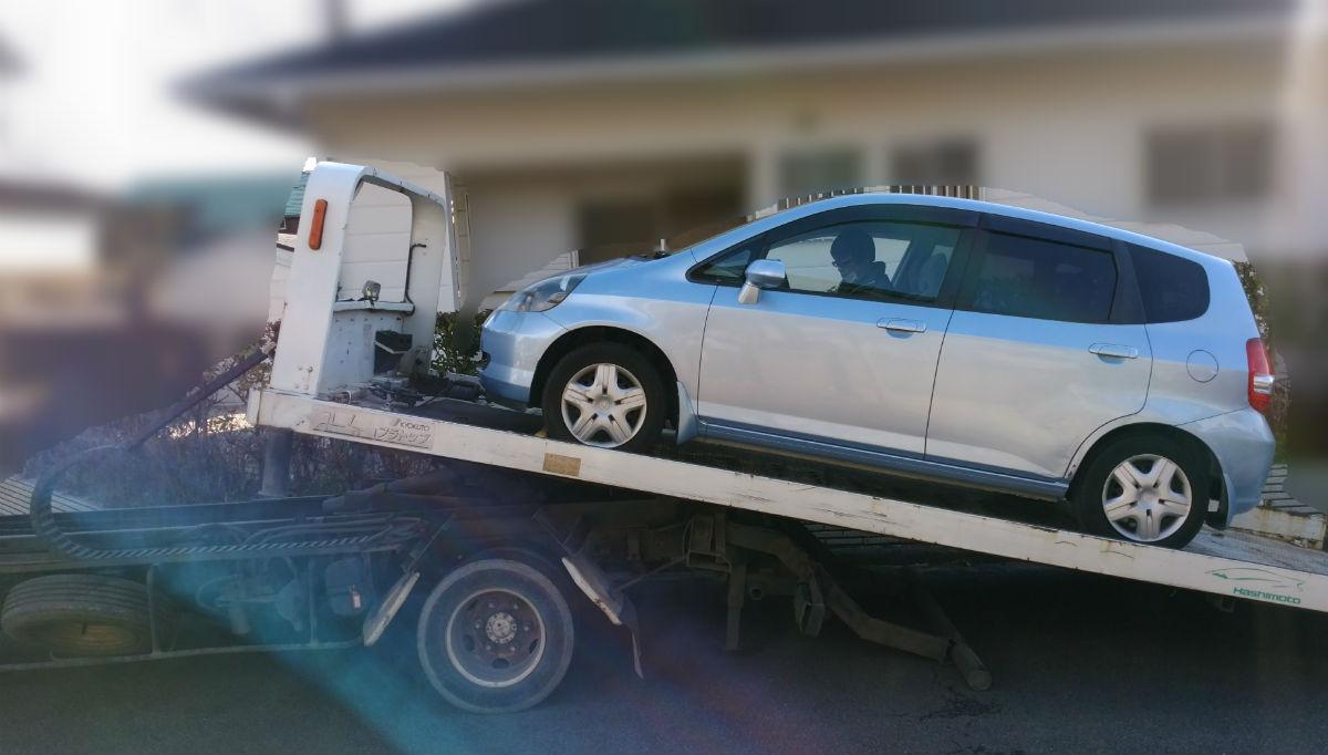 廃車ドットコムにてキャリアカーで運ばれていく青フィット